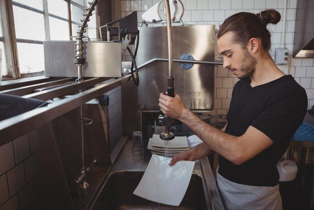 Worker washing plates kitchen