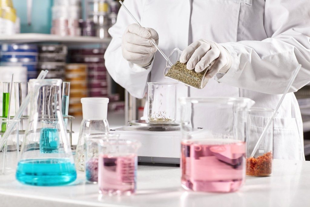person in white gown mixing chemicals inside the laboratory