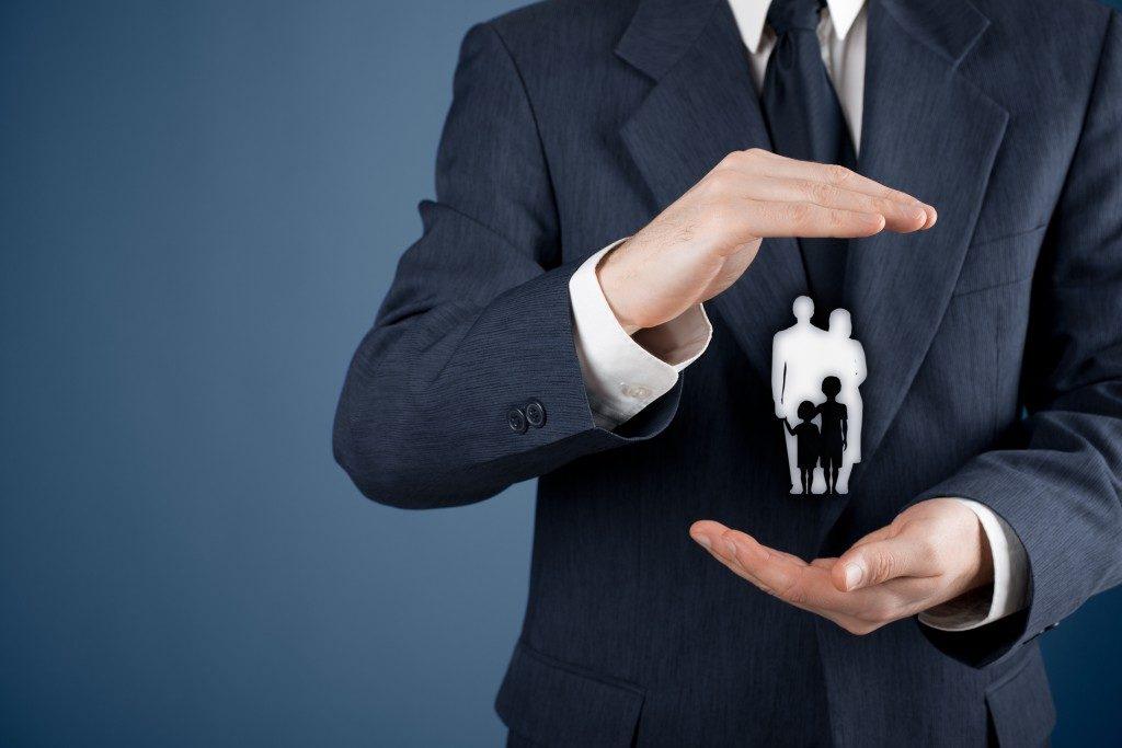 Businessman holding a family-like figure