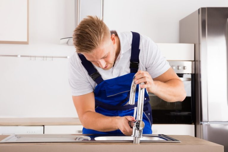 plumber fixing the faucet in the kitchen