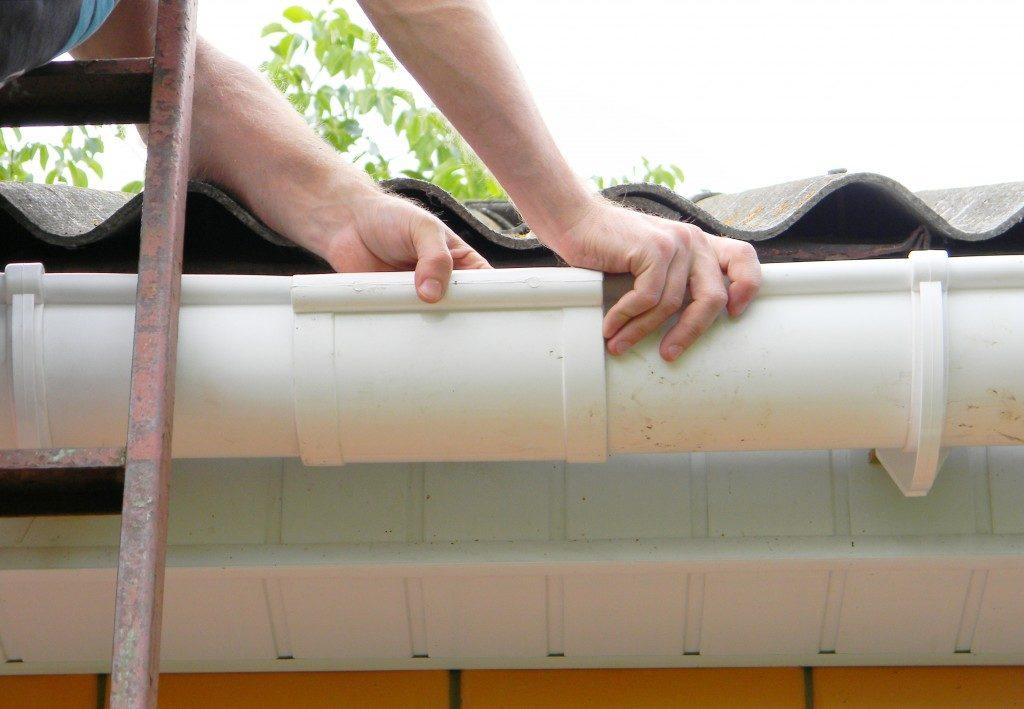 Man installing rain gutter