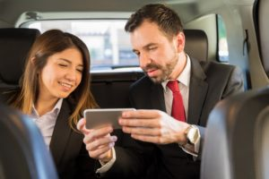 two young businesspeople riding in the backseat of a car