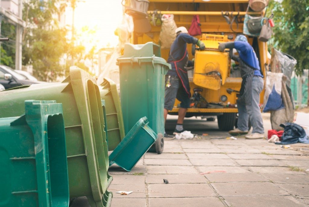 Workers collecting garbage from waste bins