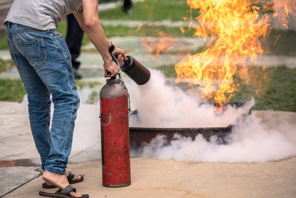 man putting out fire with a fire extinguisher