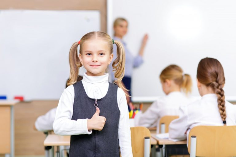 Little girl is smiling lovely and showing thumbs up while standing in the classroom