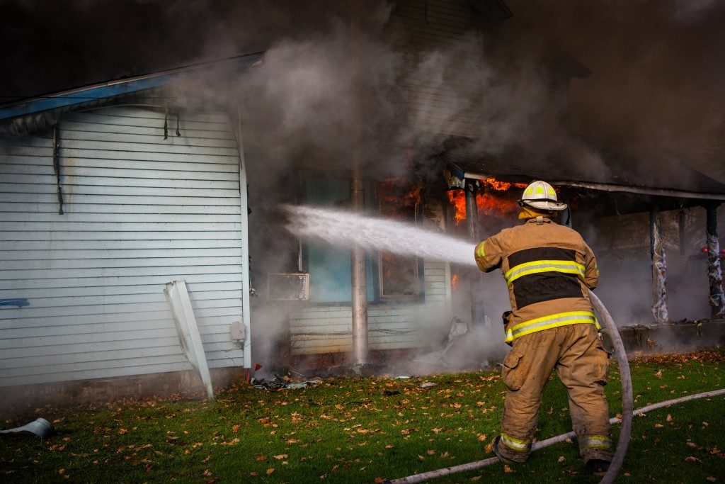 fireman putting out fire in a house