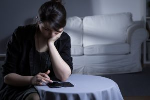 woman on her phone feeling lonely