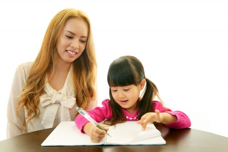 woman teaching little girl a different language