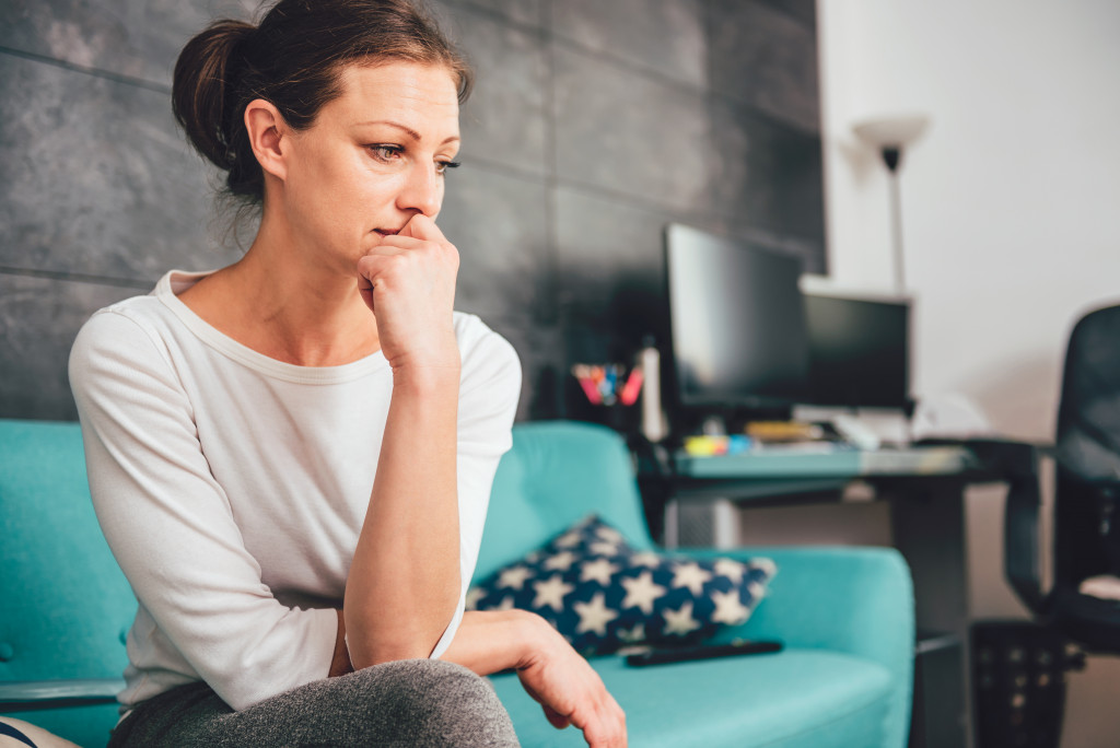 woman looking worried sitting on the couch