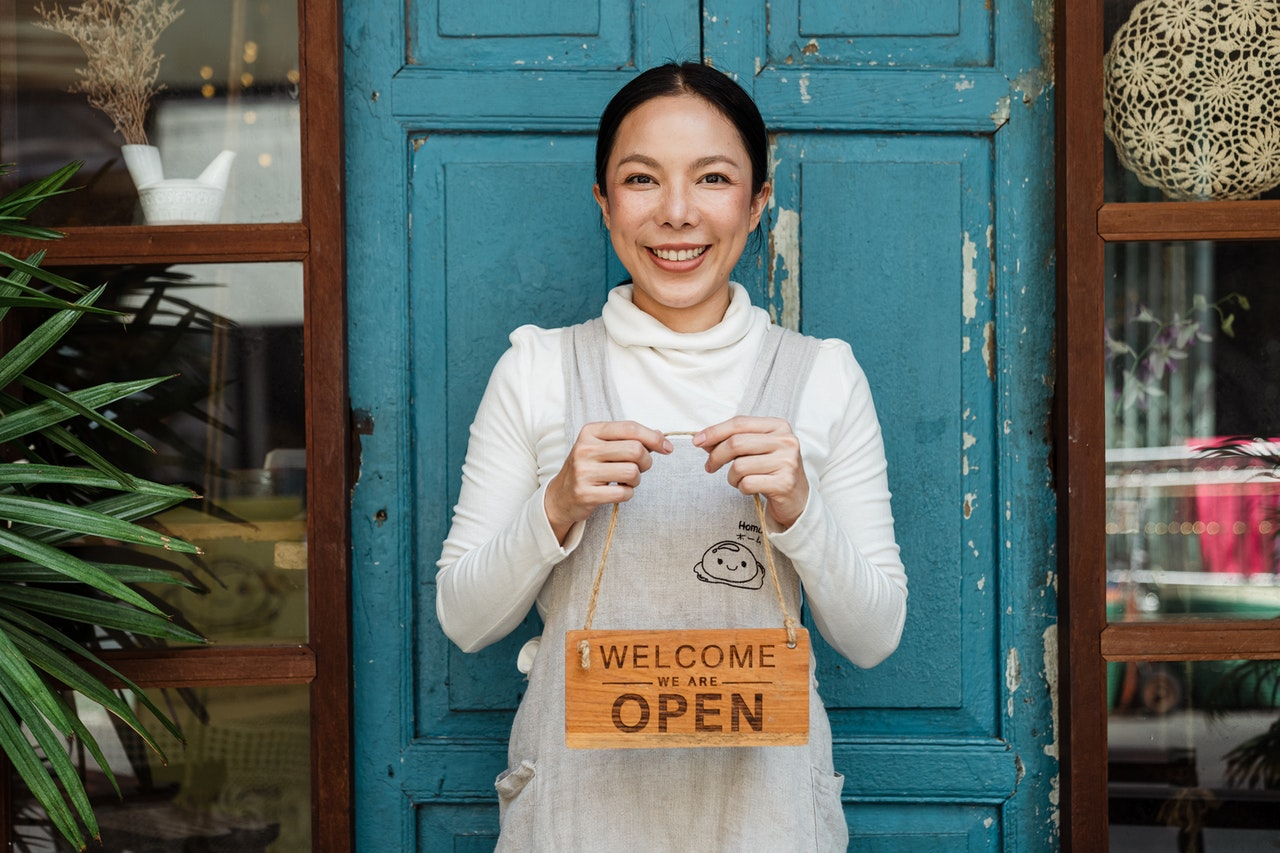 business owner holding an open signage