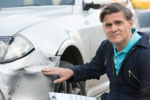 man with dented car